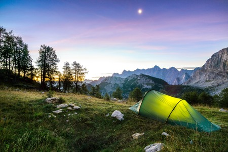 A tent glows under a moon night sky at twilight hour. Alps, Triglav National Park, Slovenia. Banco de Imagens