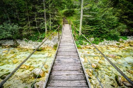 Vieux pont de planches en bois à travers la belle rivière. Surmonter un concept d'obstacle.