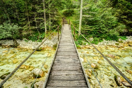 Old wooden plank bridge across beautiful river. Overcoming an obstacle concept.