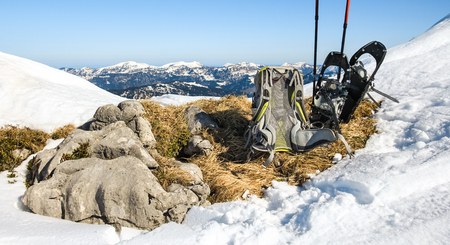 snowshoes: Winter hiking equipment. Backpack and snowshoes on top of mountain. Stock Photo