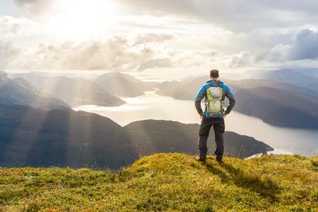 power: Man reaching summit enjoying freedom. Stunning view to coastal mountains and fjords. Hellandsnuten, Sandsfjord, Norway. Stock Photo