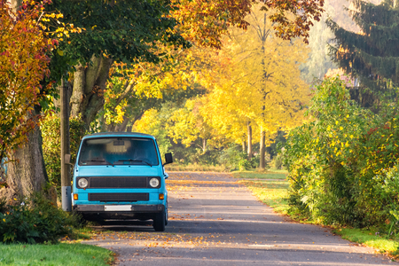 Vintage camping car on road with colorful autumn foliage trees.