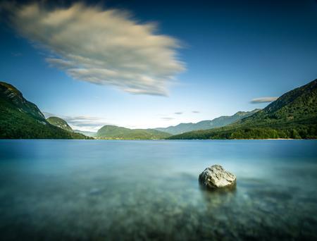 Long exposure of a rock in lake water at pebble beach.