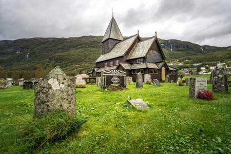Stave church and cemetery of Roldal in dramatic light on a rainy moody day. Norway.