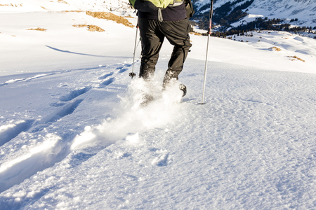 Man running downhill through deep snow with snoeshoes and hiking sticks.