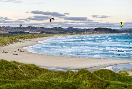 kite surfing: Kitesurfing men in action on stormy sunset evening at Brusand Beach, Norway.