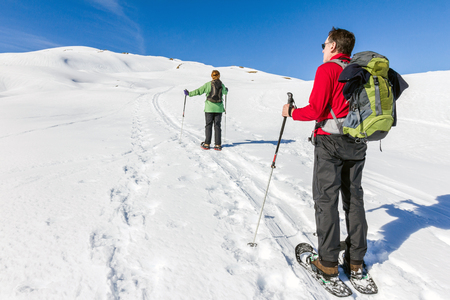 Couple is snowshoe hiking in alpine winter mountains. Bavaria, Germany.
