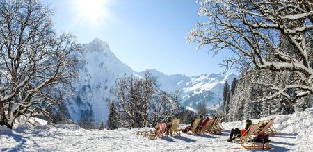 Groupe de personnes assises avec des chaises longues en montagne hivernale. Bronzer dans la neige. Allemagne, Bavière, Allgäu, Schwarzenberghuette. Banque d'images - 89992031