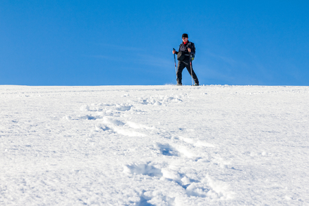 Man is snowshoe hiking through deep snow on sunny day