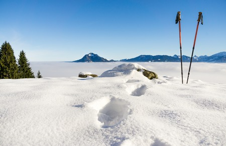 Pair of hiking sticks and footprints in snow. Sporting activity in mountains winter landscape. Allgau, Bavaria, Germany.