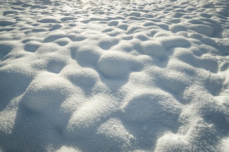 Fresh hilly snow surface background and drifting snowflakes. Bumpy snow covering winter landscape.