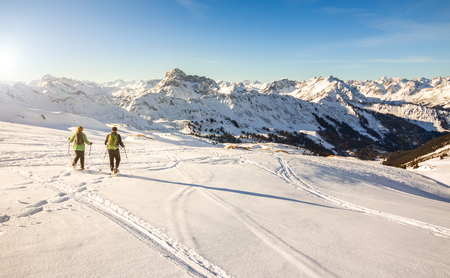 Two snowshoe hikers at sunset in alpine winter mountains. Bavaria, Germany.