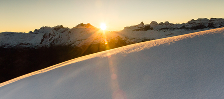 Beautiful sunrise in snowy mountain landscape. Sunbeams illuminating unspoiled powder snow. Alps, Switzerland.