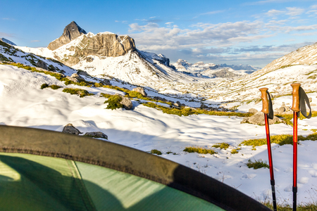 Tent and hiking sticks in snowy mountain landscape. Trekking in Swiss Alps. Hoch Turm, Charetalp, Switzerland. Imagens