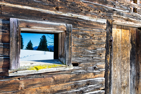 Vintage window and door of old wooden cabin mirrors winter mountain landscape. Wooden rustic background.