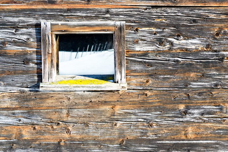 Vintage window of old wooden cabin mirrors winter landscape. Wooden rustic background. Reflections of snow field in window glass.