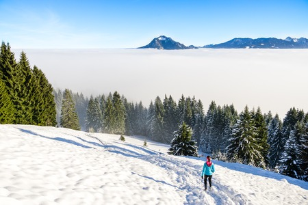 Sport, fitness inspiration and motivation. Young happy woman cross country running in mountains landscape on snow. Bavaria, Germany. Imagens