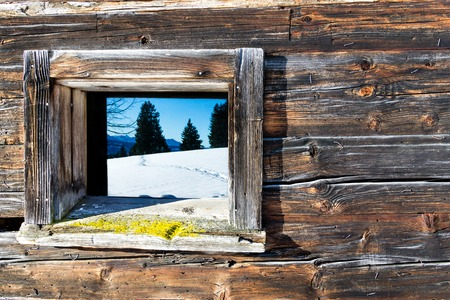 Vintage window of old wooden cabin mirrors winter mountain landscape. Wooden rustic background. Imagens