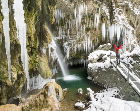 Happy man enjoying icicles and waterfall on winter hike with raised arms. Hinanger Waterfall, Bavaria, Germany