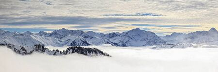 Snow-covered Allgauer mountains in low lying valley fog and trees shrouded in mist. Scenic snowy winter landscape in Alps, Allgau, Bavaria, Germany.