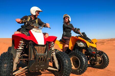 Quad driving people - happy smiling couple bikers in sand desert sunset. Reklamní fotografie