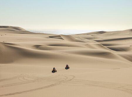 Quad driving people - two happy bikers in sand desert dunes at ocean coast beach, Africa, Namibia, Namib, Walvis Bay, Swakopmund.