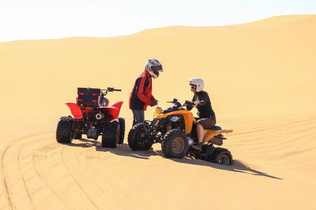 Quadbike driving people having breakdown and stuck in sand. Reklamní fotografie