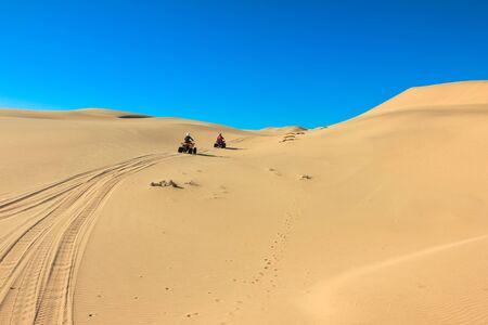 Quad driving people - two happy bikers in sand desert dunes, Africa, Namibia, Namib, Walvis Bay, Swakopmund.