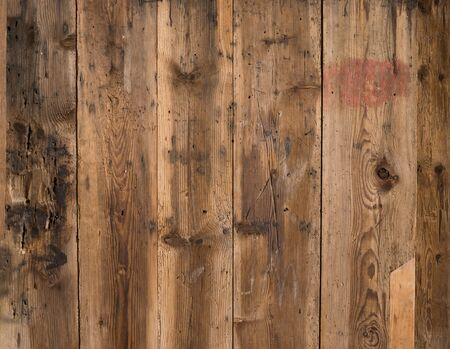 Natural brown barn wood wall. Wall texture background pattern. Wood planks, boards are old with a beautiful rustic look, style and woodworm holes.