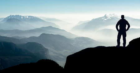 Spectacular layered mountain ranges with valley fog. Man Silhouette reaching summit enjoying freedom. Archivio Fotografico