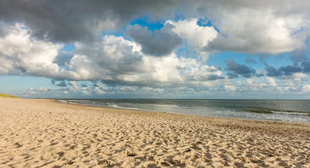 Beach sand with blue sky and dramatic clouds at coastline waterfront in soft evening sunset light. Hvidbjerg Strand, Blavand, North Sea, Denmark. Banco de Imagens