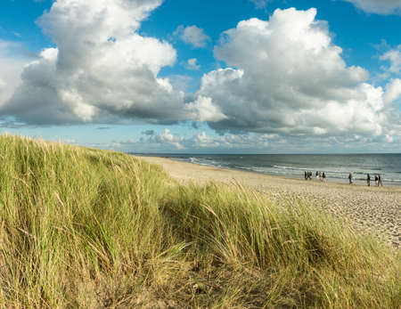 Beach sand with group of people walking at coastline. Blue sky and dramatic clouds at waterfront in soft evening sunset light. Hvidbjerg Strand, Blavand, North Sea, Denmark. Banco de Imagens
