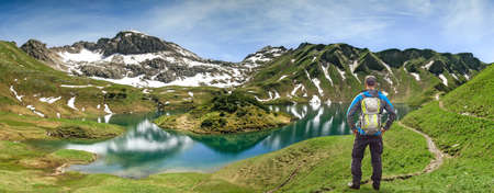Hiking Man standing at remote lake up high in the alpine mountains. Alps, Bavaria, Schrecksee. Banco de Imagens