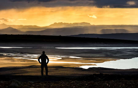 Hiker man silhouette standing at golden sunset over mountains and lake.