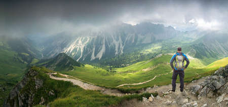 Hiker Man standing in deep hanging clouds above mountains and valley. Mystic light breaks through fog. Tirol, Austria.