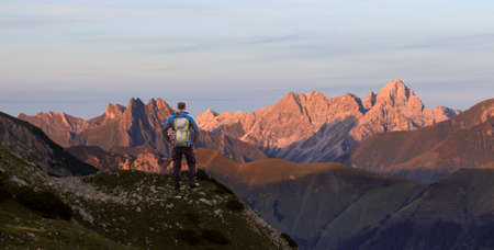Hiker Man standing at amazing view from high mountain to many other peaks at Sunset. Allgau, Bavaria, Alps, Germany. 免版税图像