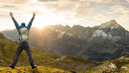 Successful Hiker Man with Backpack jumping with raised arms. Amazing sunrise in the mountains with nice lens flares and sunbeams. Alps, Allgau, Bavaria, Tirol, Austria and Germany.