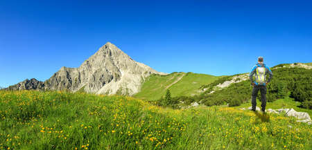 Hiking Man with Backpack on flower meadow enjoying mountains and flower in spring. Geisshorn, Allgau, Bavaria, Tirol, Austria, Germany.