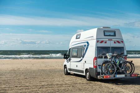 Camping Car RV standing on sand beach at waterfront on sunny day. Romo Bilstrand, Lakolk Strand, Denmark. Banco de Imagens