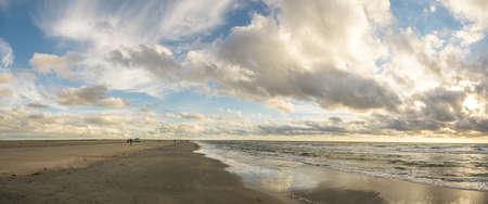 Beach sand with blue sky and dramatic clouds at coastline waterfront in soft evening sunset light. Romo Bilstrand, Lakolk Strand, North Sea, Denmark. Banco de Imagens