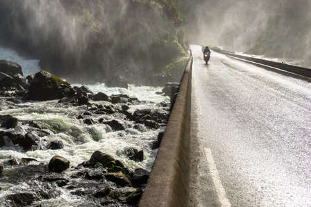 Motorbike driving fast on wet canyon valley road and bridge across waterfall river. Norway.