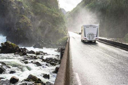 Motorhome Camper Van driving fast on wet canyon valley road and bridge across waterfall river. Norway. Banco de Imagens