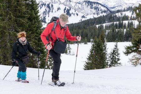 Senior couple is snowshoe hiking in alpine snow winter mountains. Allgau,  Germany. Banco de Imagens