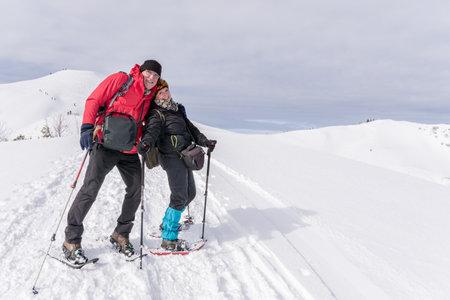 Senior couple is snowshoe hiking in alpine snow winter mountains. Allgau, Germany.