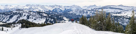 Senior couple is snowshoe hiking in alpine snow winter mountains panorama. Allgau,  Germany.