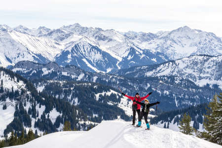 Senior couple is snowshoe hiking in alpine snow winter mountains panorama. Happy successful People with raised arms. Allgau,  Germany.
