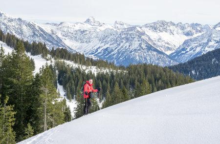 Senior man is snowshoe hiking in alpine snow winter mountains. Allgau, Bavaria, Germany.