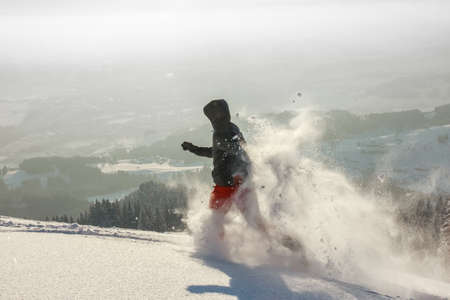 Happy Man with hood running in deep powder snow with snowshoes. Snow is spraying and splashing.