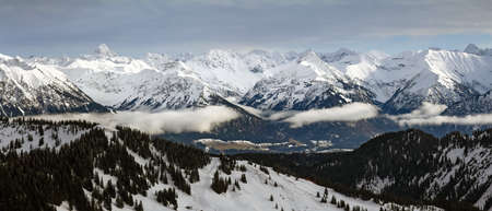 Dramatic snow covered mountains Landscape. Amazing Panoramic snowy winter landscape in Alps at sunrise morning. View from Riedberger Horn Grasgehren Ski Resort to Allgau Alps, Bavaria, Germany.