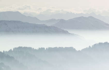 Snow Mountains in low lying inversion valley fog. Silhouettes of foggy Mountains and trees. Scenic snowy winter landscape. View from Stuiben Swiss Alps, Allgau, Bavaria, Germany. Standard-Bild